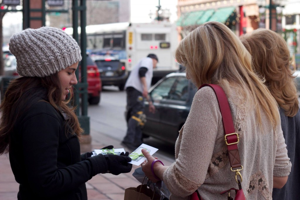 An unsuspecting passerby receives a $25 Visa Gift Card with a message to pay it forward for Colorado Gives Day.